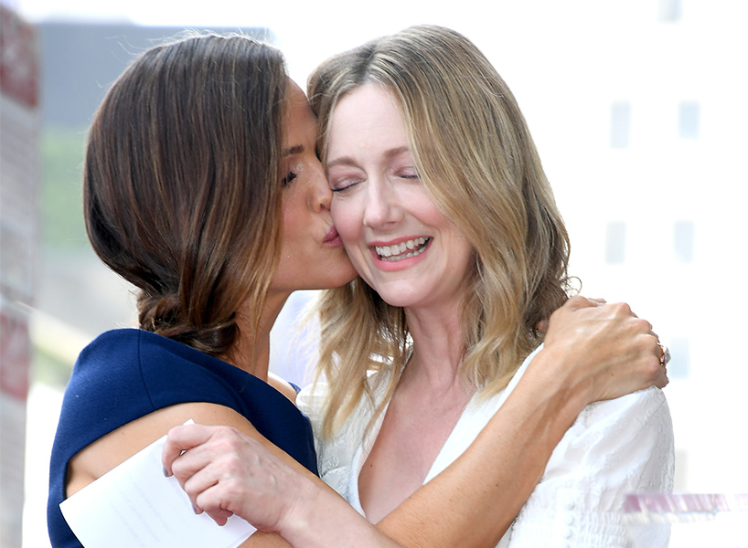 Jennifer Garner in navy dress kisses Judy Greer in white dress on cheek, in the cutest friendship