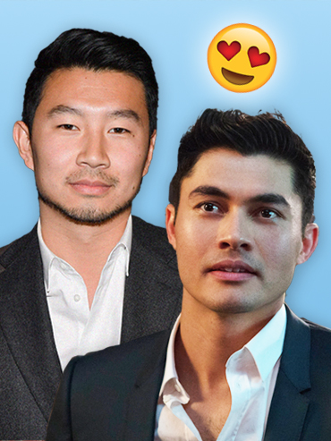 Simu Liu and Henry Golding in white shirts and black suits, with heart eye emojis above in front of blue background