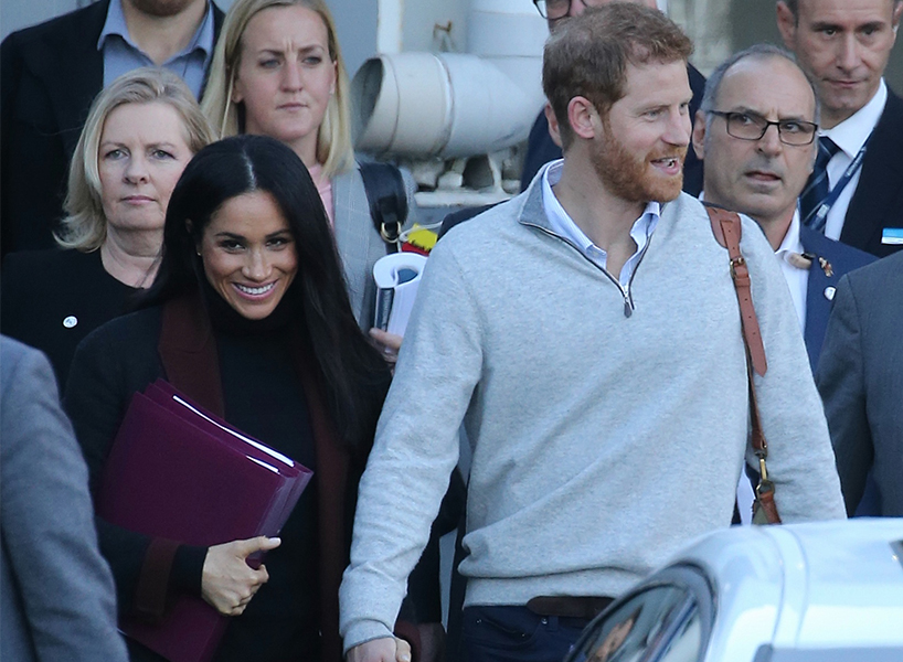 Harry and Meghan hold hands while leaving their airplane in Australia