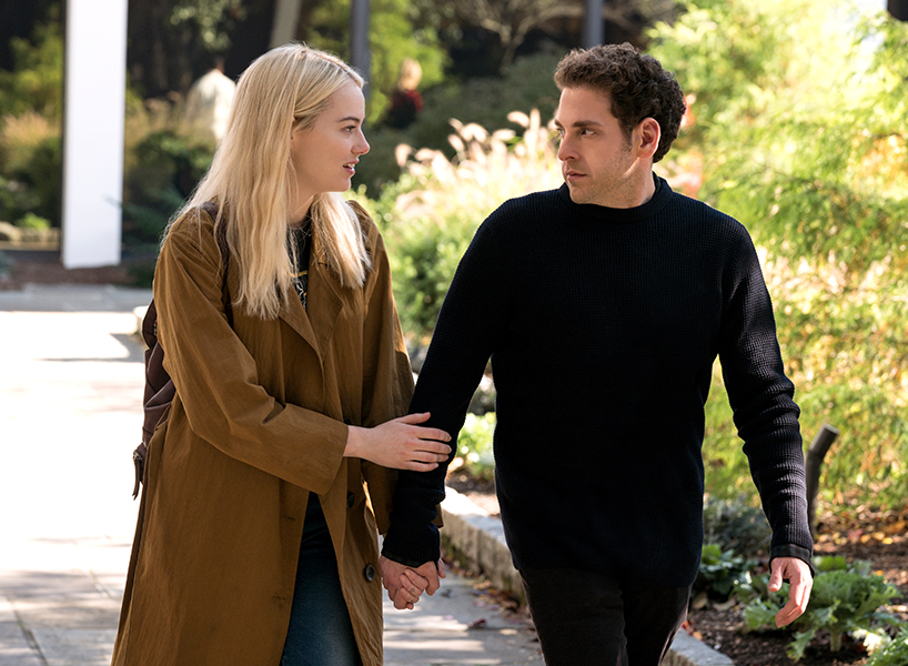 A screenshot of Emma Stone and Jonah Hill holding hands in a scene from Maniac, she is wearing a brown coat and he is wearing a black sweater and they are looking at each other