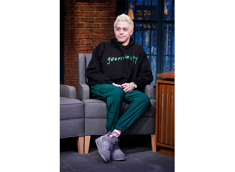 """Pete Davidson sits on a grey chair wearing green pants and a black hoodie that says """"gooniversity"""" on it."""
