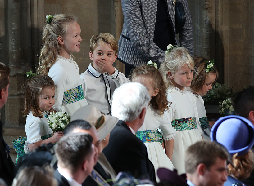 Prince George looks at the camera with his mouth covered by his hand in the crowd of flower boys and girls at the royal wedding of princess Eugenie