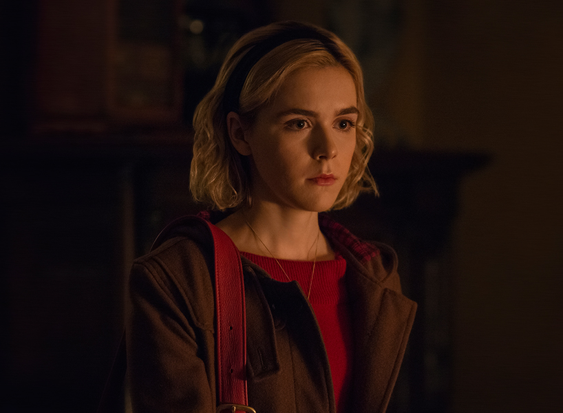 Kiernan Shipka looks serious with her hair in a hairband and wearing a red dress under a coat in this scene from The Chilling Adventures of Sabrina