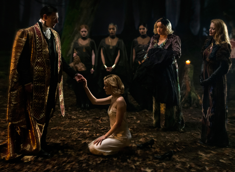 Sabrina in a scene from The Chilling Adventures of Sabrina. She is kneeling in front of a man in a big gold cloak, surrounded by serious-looking women in a forest