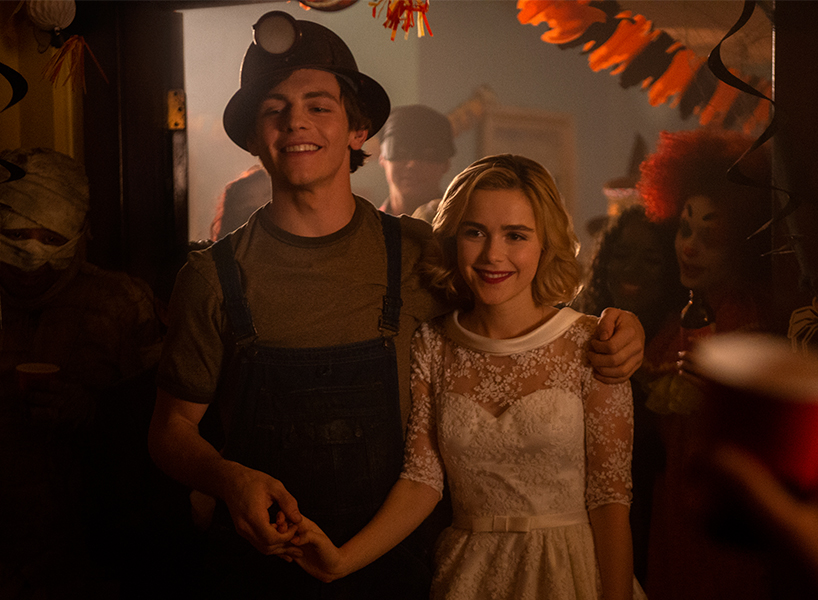 A scene from Netflix's The Chilling Adventures of Sabrina where Sabrina and Harvey attend a Halloween party dressed as a bride and a miner