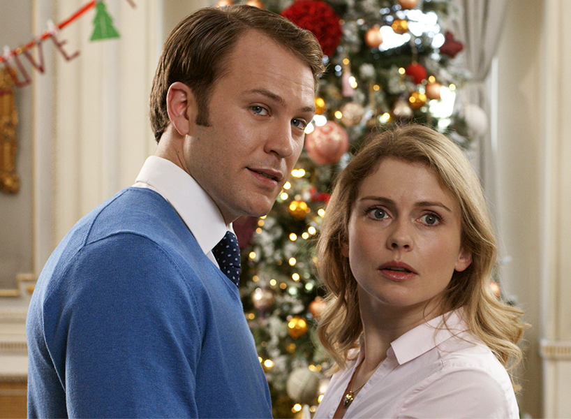 A man in a blue sweater stands close and facing a woman in a white collared blouse. There is a Christmas tree in the background. The woman looks worried. This is from a scene in Netflix's A Christmas Prince sequel, A Christmas Prince: The Royal Wedding
