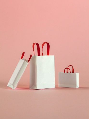Black Friday Sales 2018: white shopping bags on a pink background