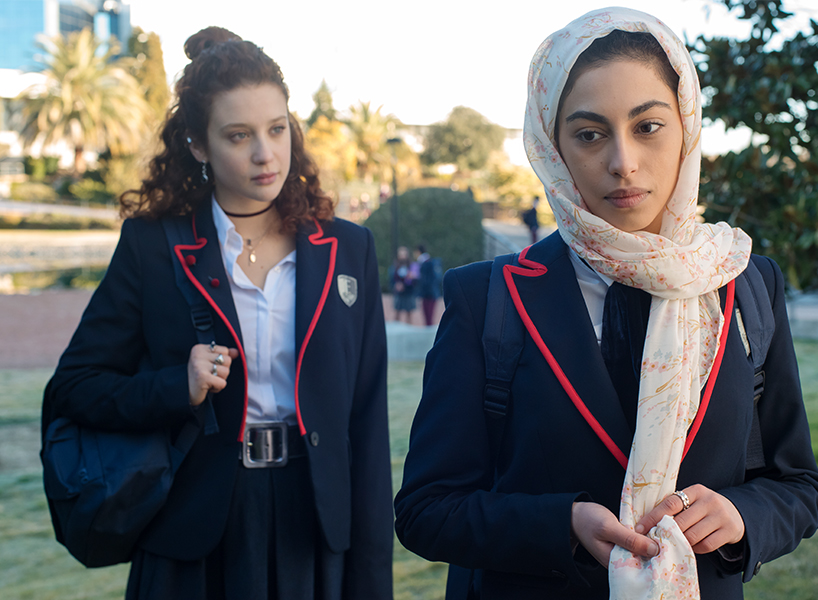 A photo of two female private school students in navy blazers, one of whom is wearing a hijab