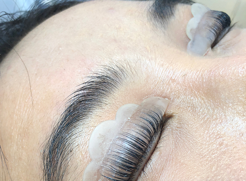 A close-up of a woman getting a lash lift treatment