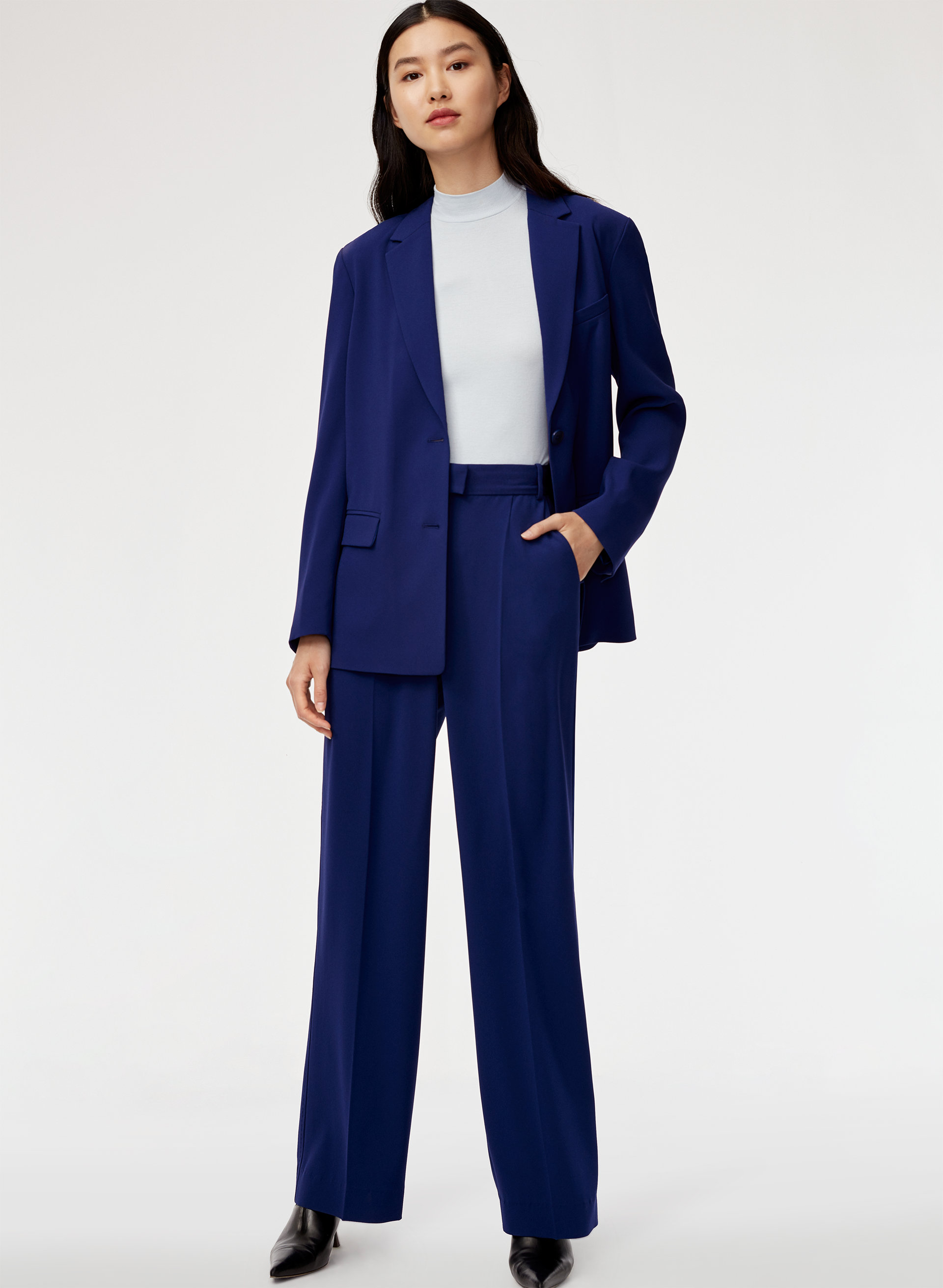 A woman wears a navy blue matching two piece suit from Aritzia.