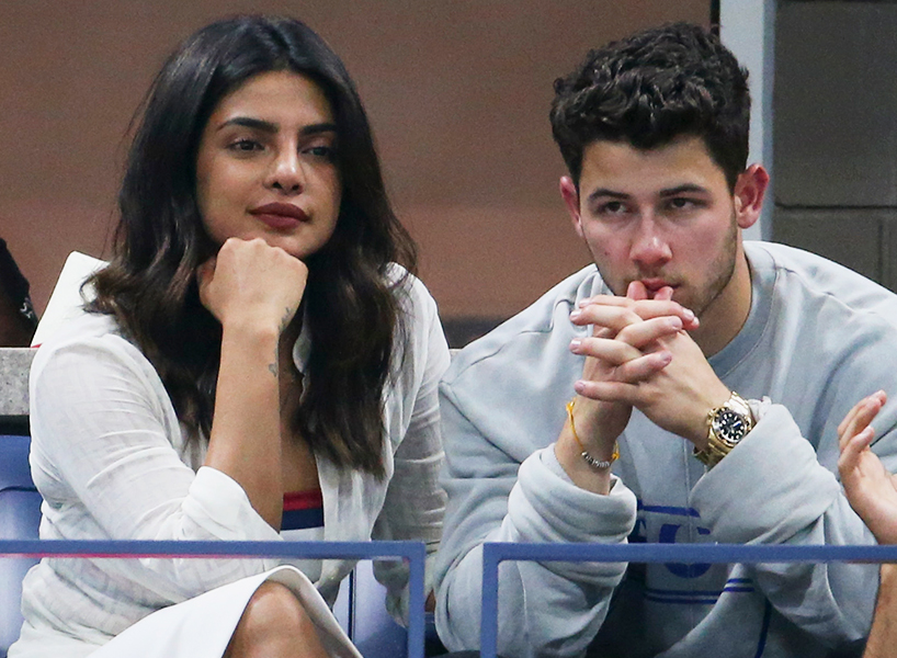 Priyanka Chopra and Nick Jonas sit in this paparazzi shot at a sports game