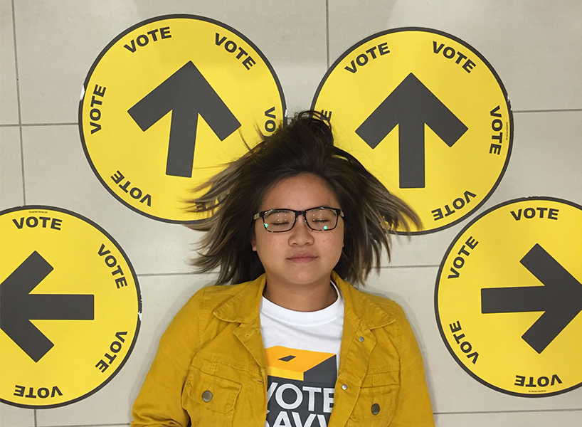 millennials voter barriers: Yvonne in yellow jacket closes sleeps on floor surrounded by yellow circles that say vote with arrows to polling stations
