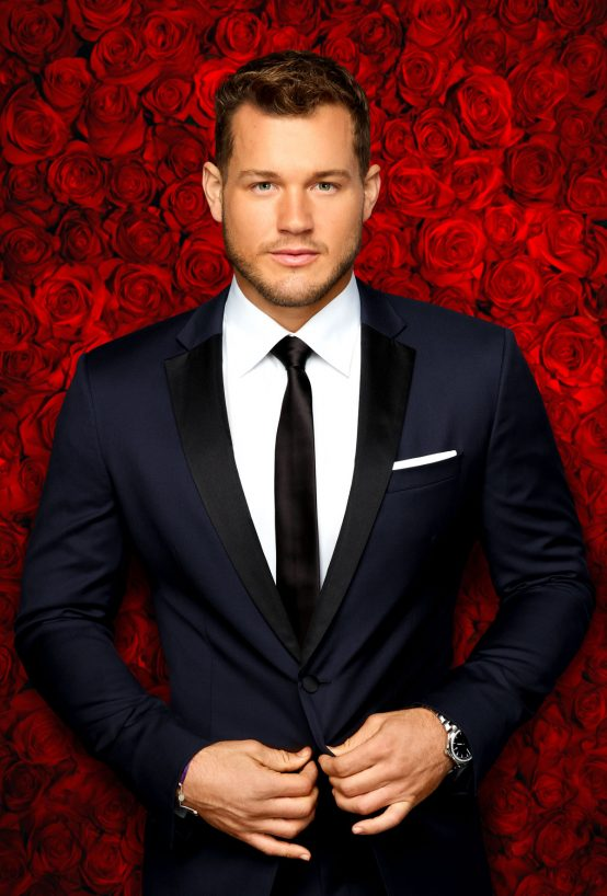 A photo of Bachelor season 23 contestant Colton Underwood in a navy suit against a red rose backdrop