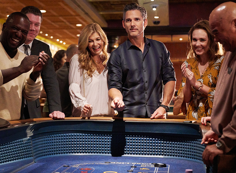 An image of a happy couple rolling the dice at a casino table surrounded by people celebrating. It's a scene from Dirty John with Connie Britton and Eric Bana.
