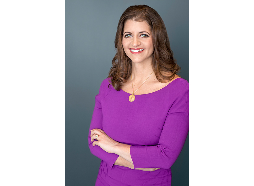 Stephania Varalli poses in this professional headshot wearing a purple top with her arms crossed