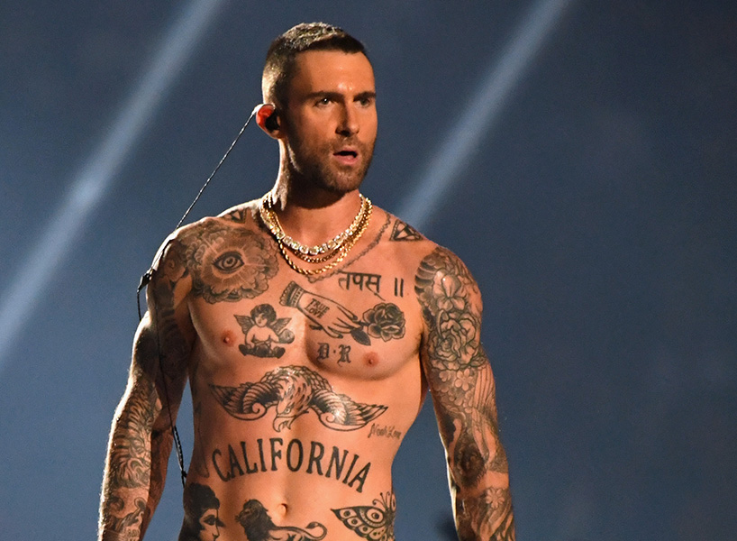 Adam Levine poses shirtless at the end of his Super Bowl halftime show performance.