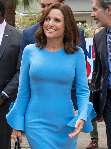 Julia Louis-Dreyfus wears a blue dress and walks in a scene from Veep, now streaming on Crave