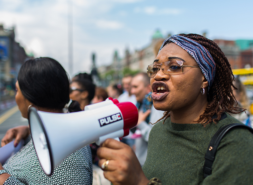 A photo of a Black woman with glasses speaking into a bull horn