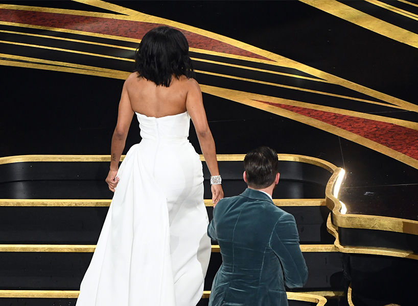 Regina King and Chris Evans ascending the stairs to the stage at the Oscars