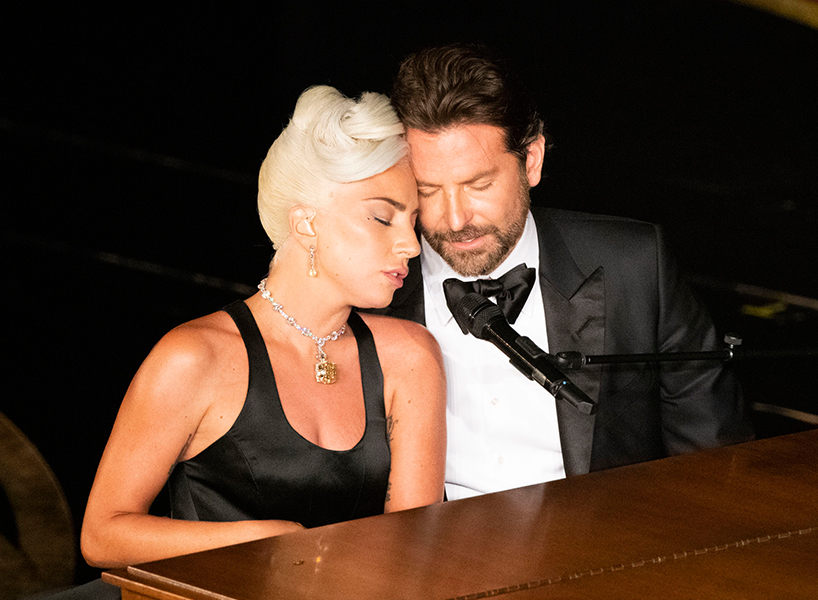 "Lady Gaga and Bradley Cooper get cosy behind a piano bench during their Oscar performance of ""Shallow"""