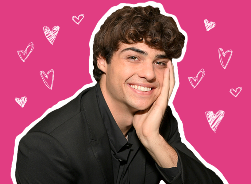 Noah Centineo has his face resting on his hand while he smiles at the camera, the photo is cut out and on a pink background with hearts around it