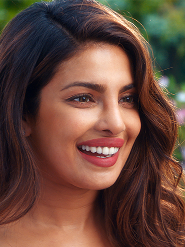 Priyanka Chopra smiles in this scene from Isn't It Romantic, a parody on rom coms. She is on an angle and looking at someone in front of her who isn't pictured. Her hair is down and wavy and it appears to be summer.