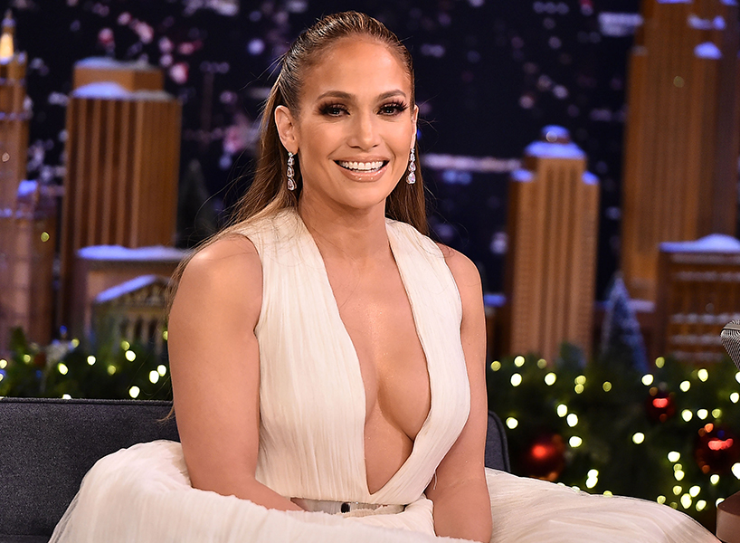 Jennifer Lopez sits on a talk show couch and smiles in a white low-cut gown