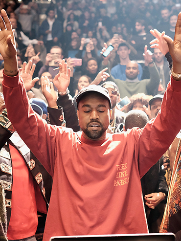 Kanye West lifts his hands in the air and appears to be praying at a concert in New York City surrounded by a crowd. The photo is used in a story about Kanye West's church service.