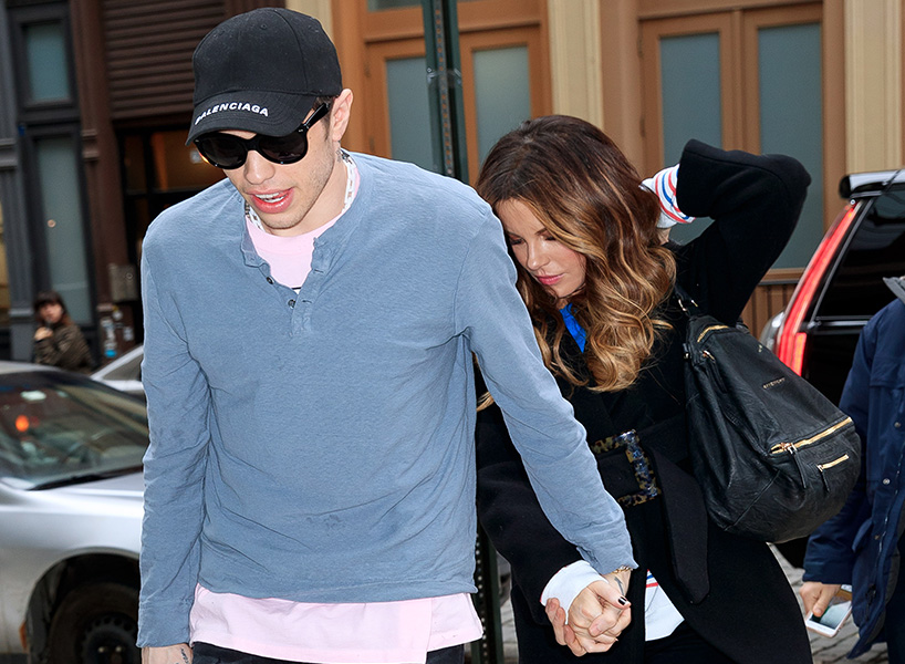 Pete Davidson and Kate Beckinsale hold hands as they walk on the sidewalk looking down in this paparazzi photo