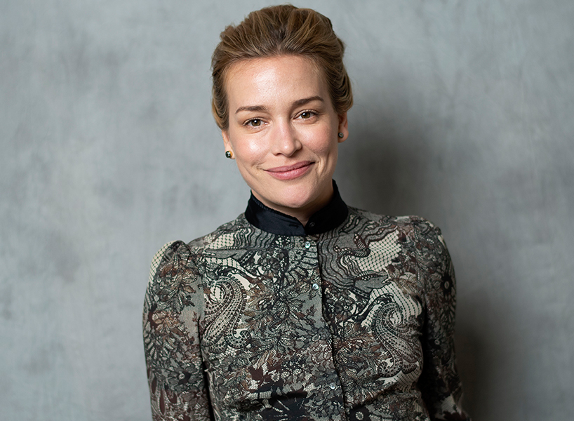 Piper Perabo poses in a patterened jacket with her hair back and smiling at the camera against a grey background