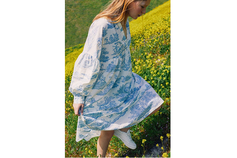 A model wears a white and blue toile print dress in a field of yellow flowers for the Urban Outfitters Laura Ashley Dresses campaign