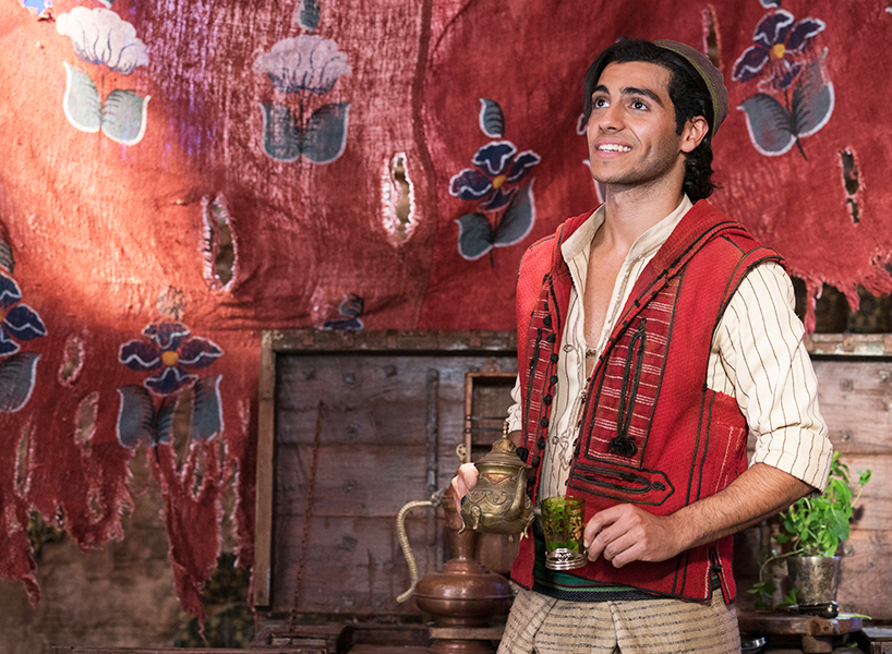 Aladdin's Mena Massoud smiles in a scene from the Disney movie. He is dressed as Aladdin and holding a tea pot and cup and in what appears to be a tent