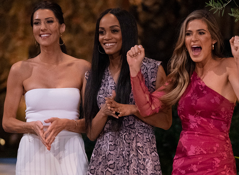 Becca Kufrin, Rachel Lindsay and JoJo Fletcher all stand in a line and smile and cheer during The Bachelorette reunion special
