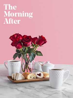 Coffee with red roses and pastries on a marble counter with a pink wall background