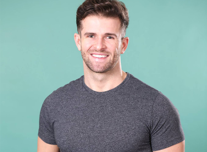 Season 15 Bachelorette contestant Jed W. wearing a short-sleeved grey shirt as he smiles and poses for the camera.
