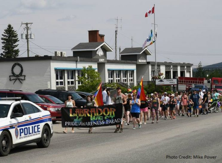 A small crowd in Labrador marching down the street holding flags and signs