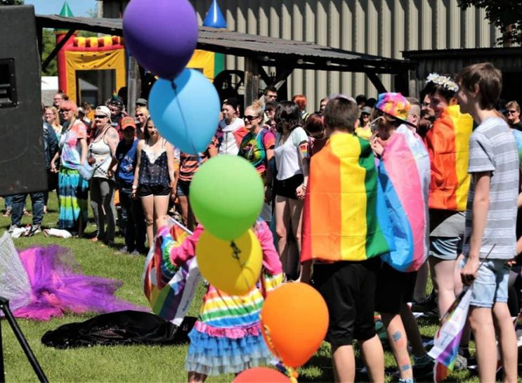 A crowd of people wearing rainbow flags and colourful outfits, with rainbow balloons in the foreground