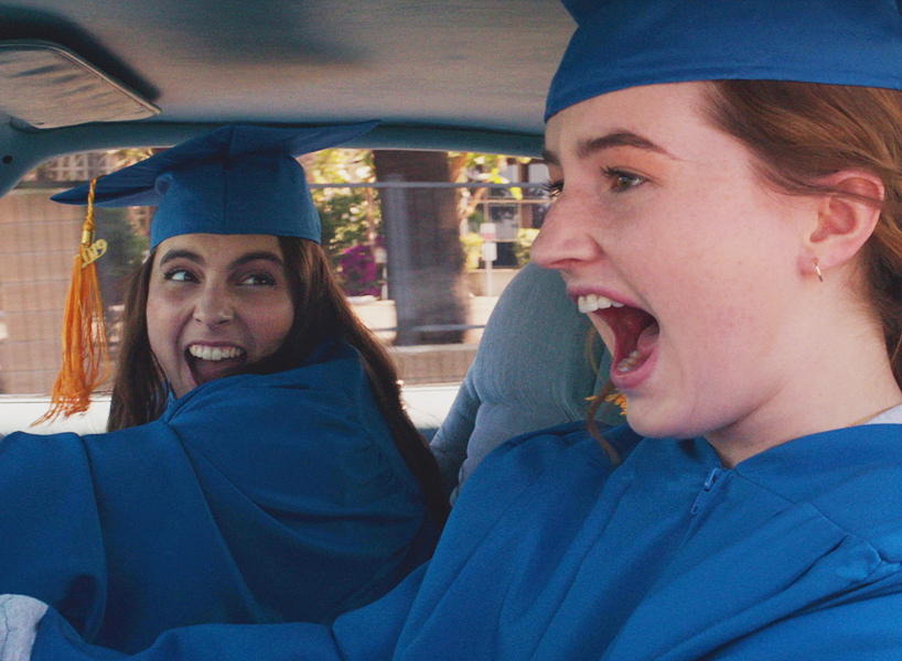 Booksmart: Two teenagers wearing graduation gown and cap screaming as they're driving.