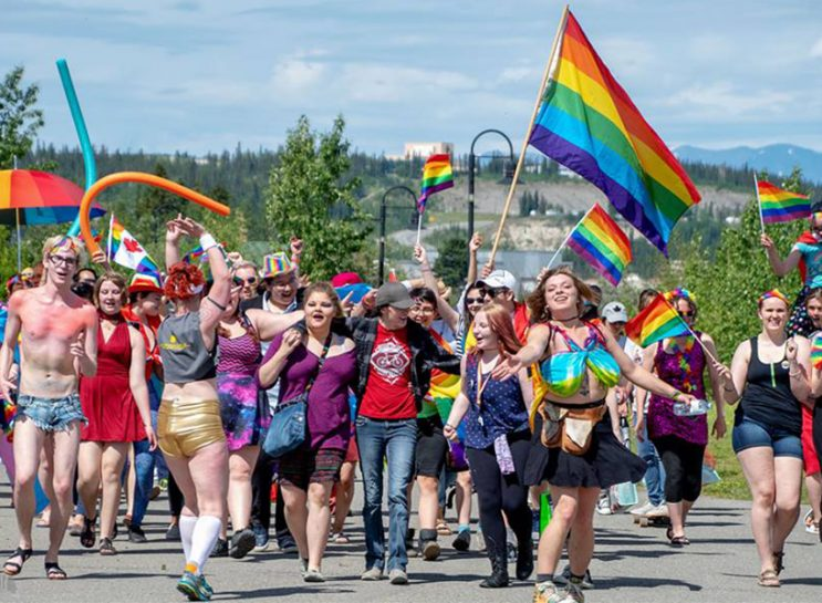 A group shot of Pride attendees in Whitehorse walking with their arms around one another and carrying rainbow flags