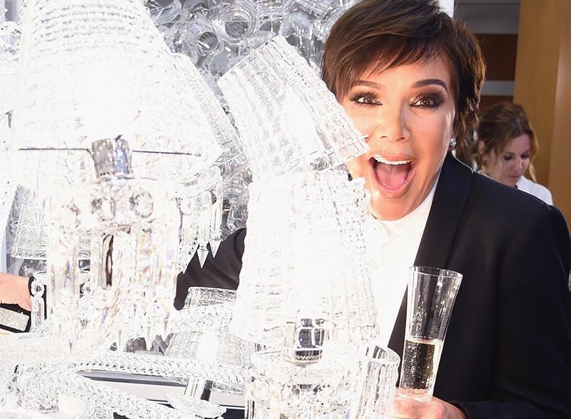 Kris Jenner smiles with a glass of champagne in hand behind a large chandelier