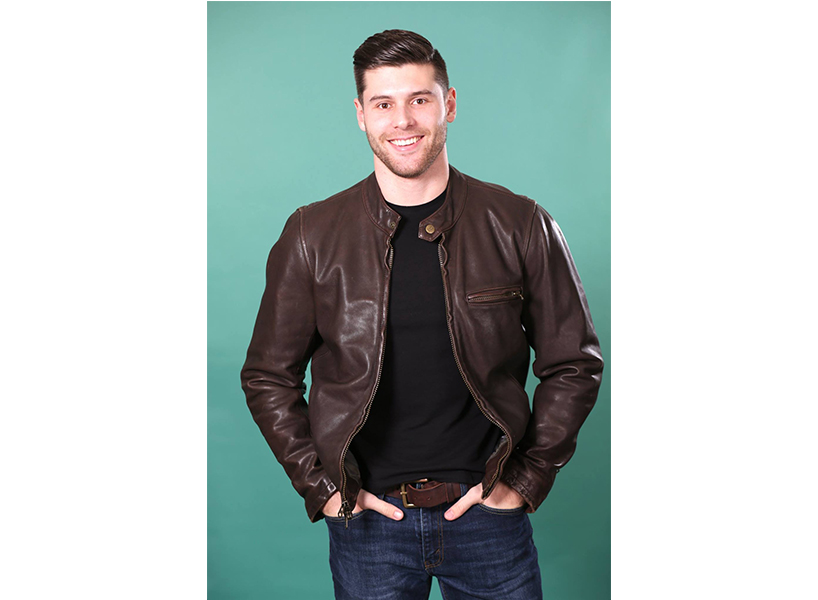 Matteo V, a contestant on The Bachelorette, poses for a photo wearing a brown leather jacket and black t-shirt standing against a teal background