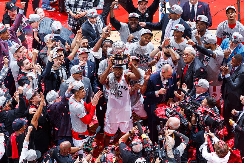 Toronto Raptor Kawhi Leonard holds up a trophy as fans cheer around him