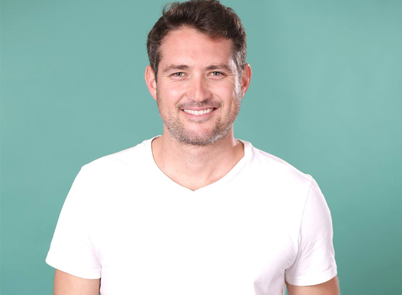 The Bachelorette's Grant E smiling and wearing a plain white t-shirt.