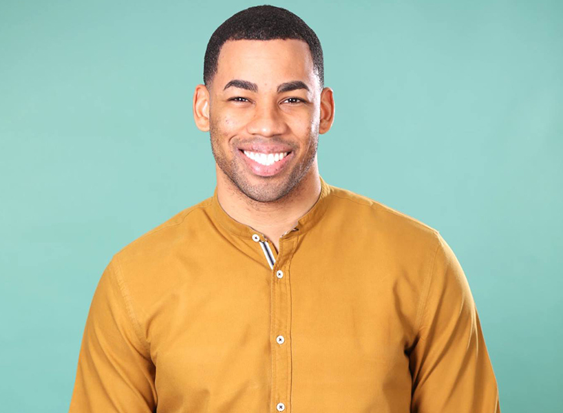 Mike J from the bachelorette wearing a mustard coloured shirt and smiling.