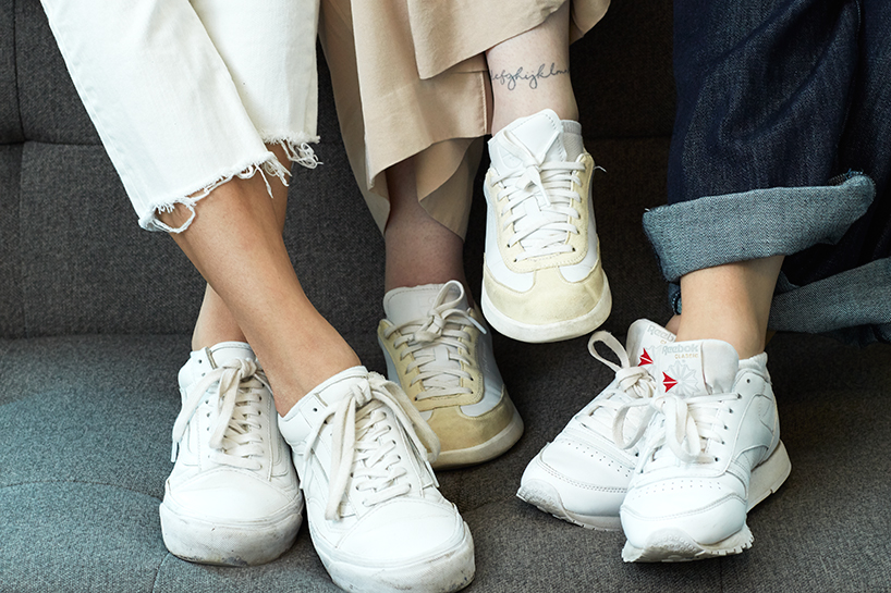A close-up of three pairs of white sneakers worn by three women sitting on a grey couch