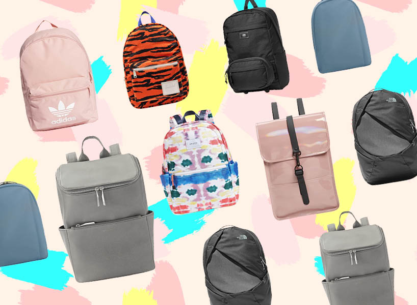 Different backpacks against a pink painted background.