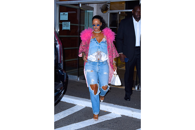 Rihanna wearing ripped jeans and a pink fluffy jacket