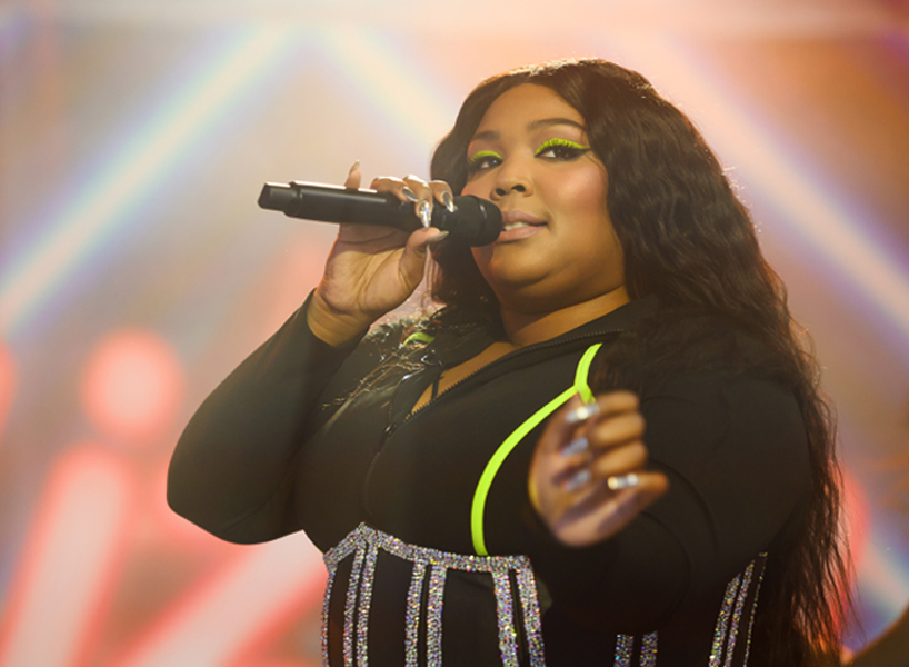 Singer Lizzo performs on-stage wearing a black bodysuit with a bright green stripe