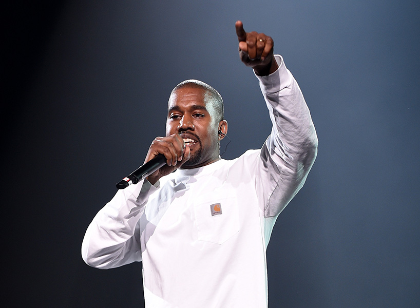 Kanye West wears white pants and a white long-sleeve tshirt while performing on-stage