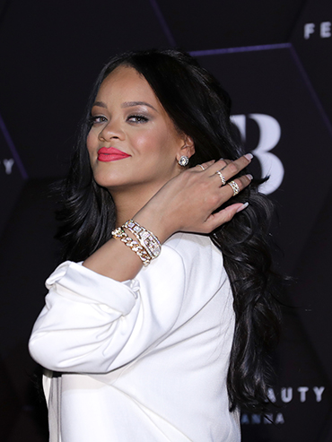 Singer Rihanna wears a white top and pushes her hair over her shoulder while smiling at the camera